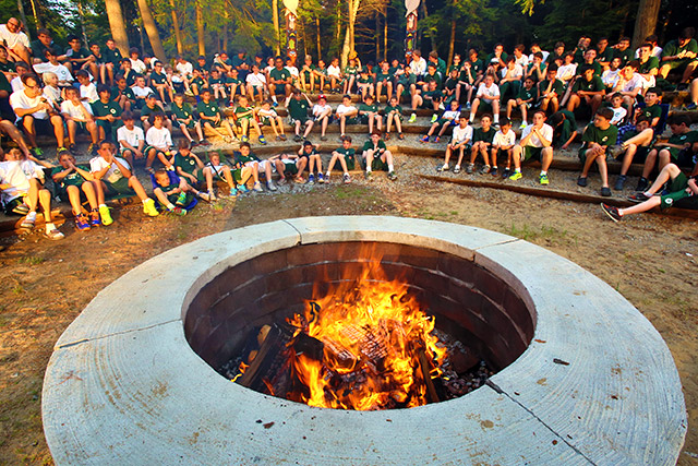 Campfire ring with many boys gathered around it