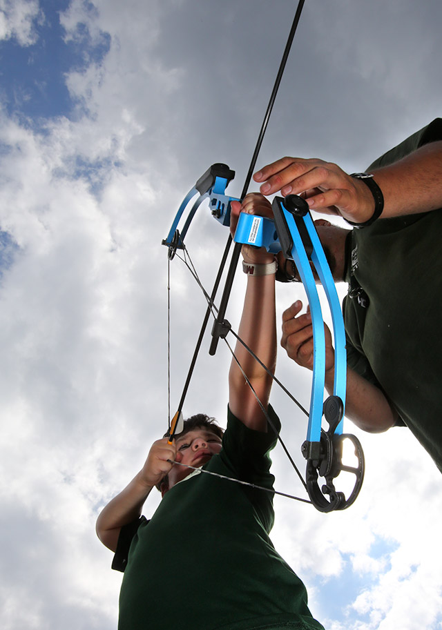 A teacher shows a boy how to shoot a bow