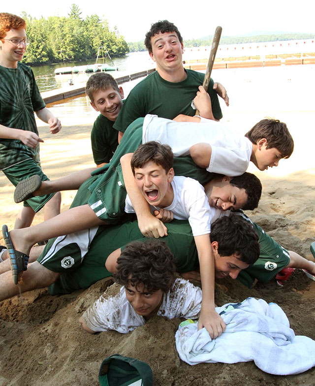 A dog pile of laughing boys having the best time at summer camp
