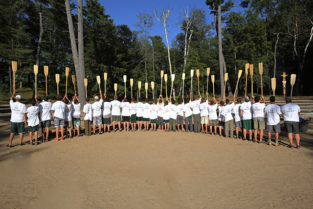 Boys gathered in a semi-circle holding oars up in a symbolic gensture
