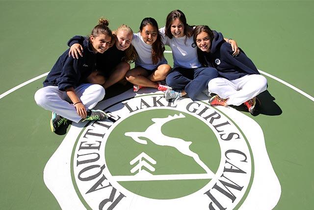 Girls together around camp logo