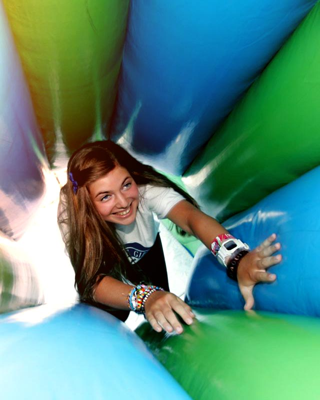 A girl crawling through a green and blue tunnel