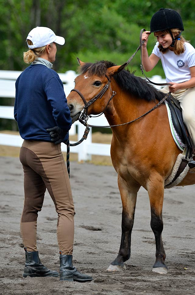 An instructor works with a girl on horseback