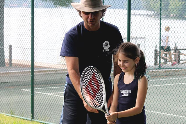 Girl learning to play tennis