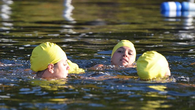 Girls swimming across the lake